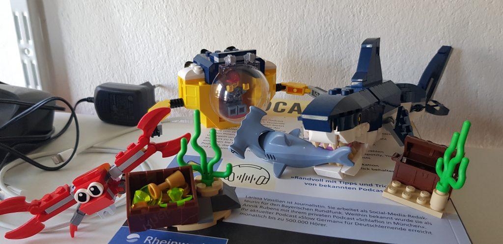 Das Bild zeigt eine typische UNterwasserszene in der ein mächtiger Megalodon einen hilflosen Hammerhai wegbeißt. Im Hintergrund beobachtet Jason Statham die Szene in seinem Forschungs-Tauchboot und im Vordergrund ergreift eine überdimensionale Strandkrabbe die Flucht.